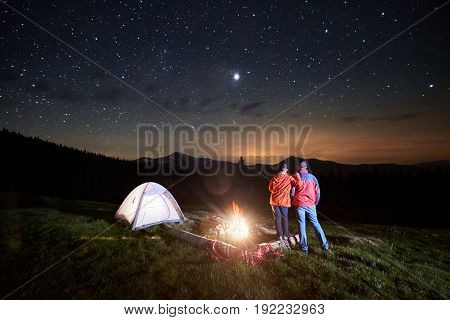 Night Camping In The Mountains. Rear View Of Romantic Couple Tourists Standing At A Campfire Near Il