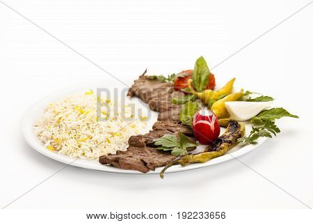 Low angle view of Persian lamb kebab called kebab barg. Tender meat pieces taken of the skewer and served with rice herb and peppers on a plain plate. Studio shot over white table top background.
