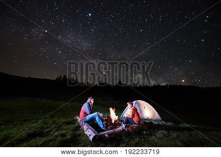 Night Camping. Man And Woman Tourists Sitting At A Campfire Near Illuminated Tent Under Night Starry