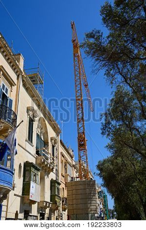 VALLETTA, MALTA - MARCH 30, 2017 - Traditional city centre buildings with a crane in the foreground Valletta Malta Europe, March 30, 2017.