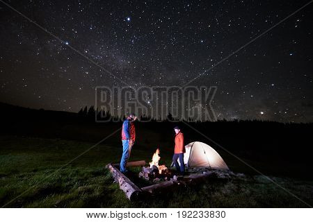 Night Camping In The Mountains. Couple Tourists Standing At A Campfire Near Illuminated Tent Under N