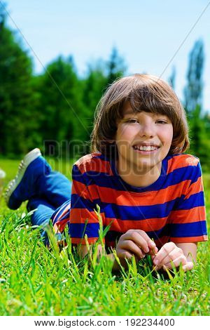 Cheerful boy lying on a green lawn on a sunny summer day. Happy childhood.