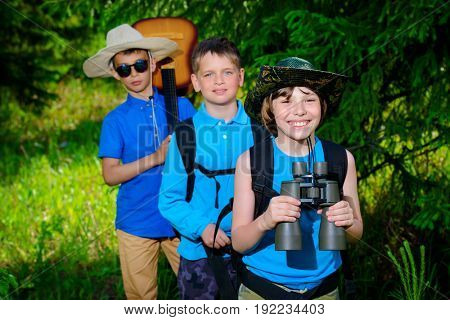 Three boys friends go hiking with backpacks. Summer holidays. Outdoor activities.