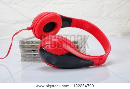 Musical equipment - Red headphone and music CD on a white background. Isolated
