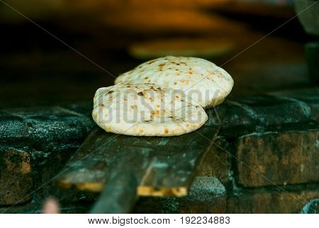Fresh round pita is taken from the oven. Prepatation of tradition arabic bread