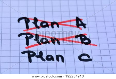 Crossing out plan A and plan B written plan C on notebook page