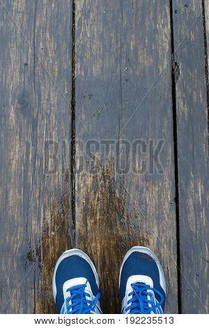Feet on the background of wooden boards - wet after the rain. Texture of wet wood and shoes - the top view. Conceptual photography alone.