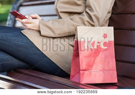 Minsk, Belarus, june 21, 2017: lunch bag KFC on a bench next to a woman with a mobile phone. Kentucky Fried Chicken (KFC) is world's second largest restaurant chain almost 20,000 locations globally.