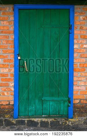 Old barn with wooden doors of green color and brick wall