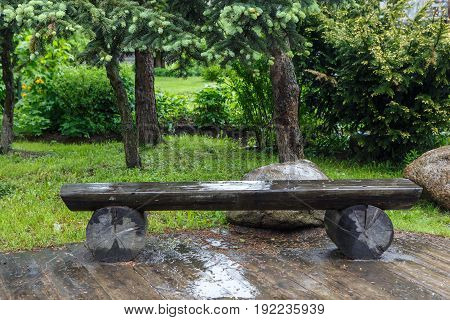 Wet wooden bench in the Park is wet after rain. Shop like a designer the idea of making of wood for outdoor decoration.