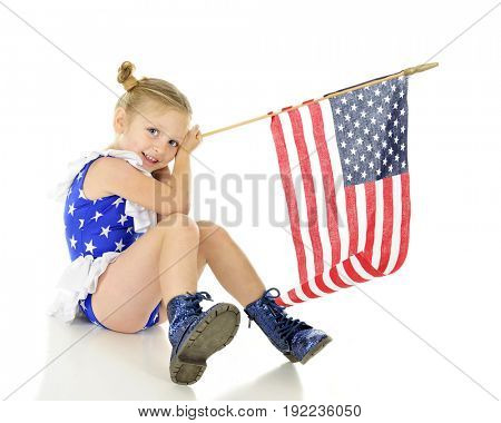 An adorable preschooler sitting in her patriot outfit, shyly displaying her American flag.  On a white background.