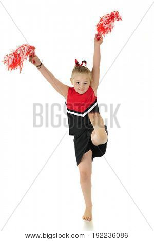 A young elementary cheerleader in uniform, kicking her bare foot.  Motion blur on foot and pom poms. On a white background.