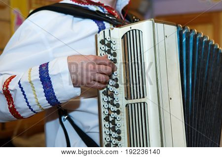 Accordion in the hands of the musician. Slavic Russian national costume with embroidery. Folk musical art of the rural traditional.