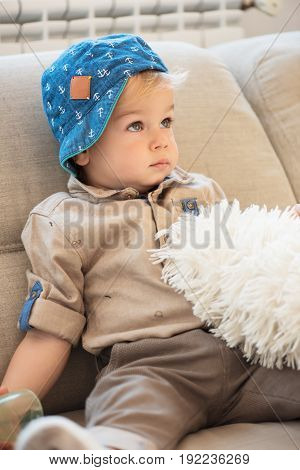 Portrait Of Nicely Dressed Little Boy With Blue Eyes Sitting On The Sofa And Looking Up.
