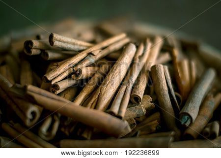Heap of cinnamon sticks in the arab market in knitted basket