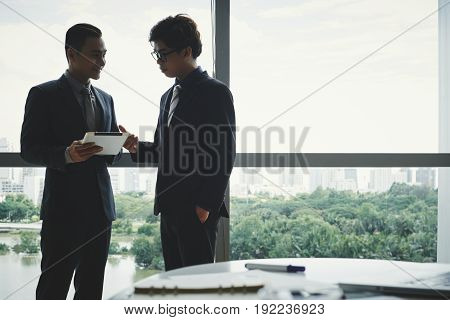 Handsome Asian managers having informal meeting while standing at panoramic window of spacious boardroom, picturesque cityscape on background