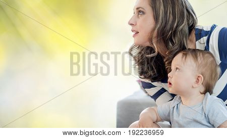 closeup of mother and her boy child looking upwards to the rays of light on green background to the future
