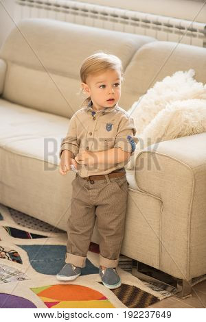 Nicely Dressed Little Boy With Blue Eyes Standing Up In Front Of Sofa.