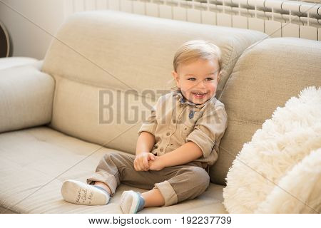 Nicely Dressed And Happy Little Boy With Blue Eyes Sitting On The Sofa.