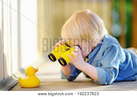 Cute Little Boy Playing With Rubber Duck And Plastic Binoculars Outdoors