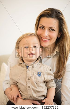Portrait Of Beautiful Mother And Little Son Sitting In Her Lap. Family Values.