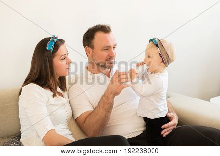 Mother and father sitting on the sofa and playing with their beautiful baby girl. Family values.