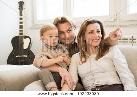 Portrait Of Happy Parents Sitting On The Sofa With Their Beautiful Baby Boy.  Finger Pointing. Famil