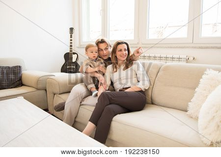 Happy Parents Sitting On The Sofa With Their Beautiful Baby Boy.  Finger Pointing. Family Values.