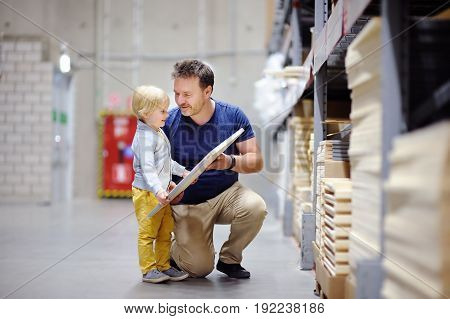 Middle age father with little boy choosing the right furniture for their apartment in a modern home furniture store. New home for family with kids