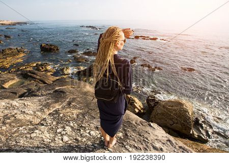 Young woman with blonde dreadlocks standing on the rocky shore of the ocean toward the sun. View from the back.