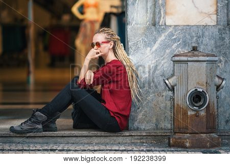 Young woman in sunglasses with blonde dreadlocks sitting thoughtfully on the street outside the clothing store.