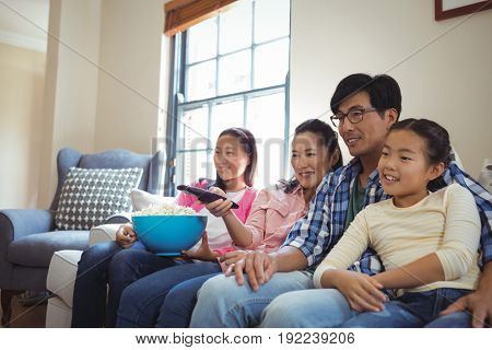 Smiling family watching television together in living room at home