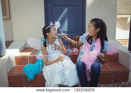 Siblings having fun in fairy costume at home