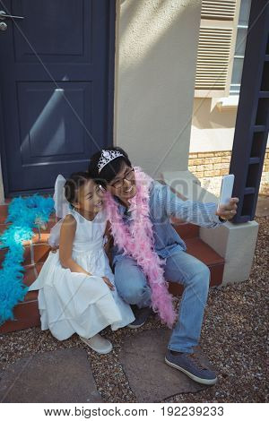 Father and daughter in fairy costume taking a selfie at home