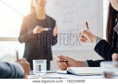 Close-up shot of female finger pointing at young Asian speaker giving presentation in modern boardroom with panoramic windows, blurred background