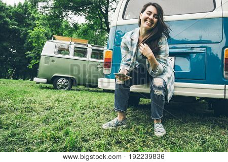 pretty stylsih woman stits near retro van in rainy weather