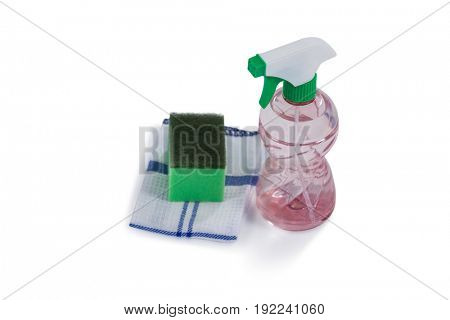 Close-up of spray bottle, scouring pad and napkin cloth on white background