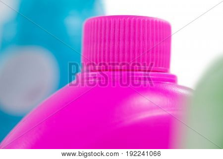 Close-up of pink detergent container on white background
