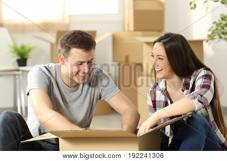 Couple moving home packing belongings in a cardboard box sitting on the floor of the living room
