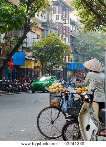 Street vendor transporting and selling fruit in the streets of Hanoi Vietnam