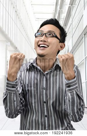 Success winner Asian businessman looking up, standing outside office.