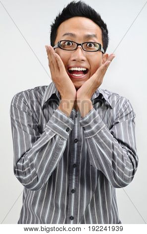 Shocked businessman portrait, Asian business man face expression, hands on cheek.