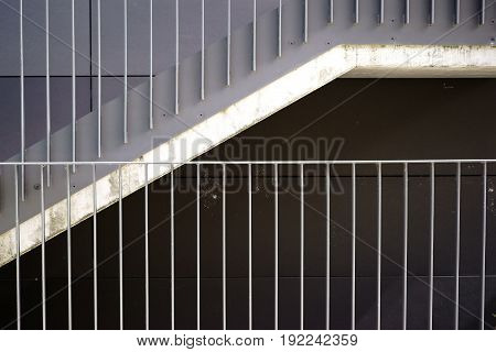 The detail of a modern staircase with a railing made of stainless steel