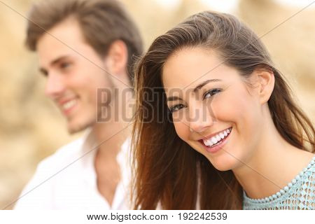 Happy beautiful girl with white smile posing and looking at you with an unfocused man in the background