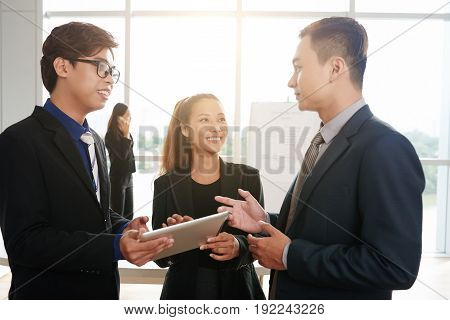 Cheerful Asian financial managers chatting animatedly with each other while standing in spacious open plan office with panoramic windows