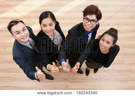 Directly above view of cheerful Asian white collar workers looking at camera with wide smiles and showing thumbs up