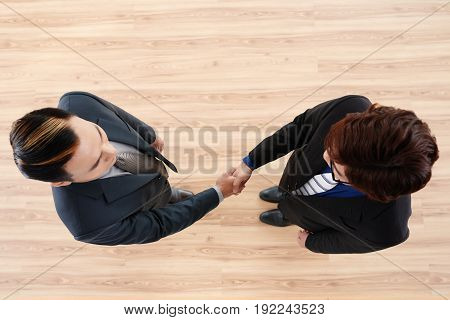 Directly above view of unrecognizable business partners shaking hands as sign of successful completion of negotiations