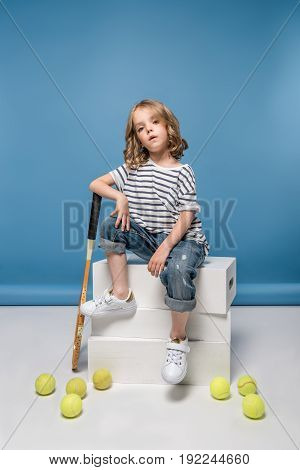 adorable little girl sitting on white boxes with tennis raquet and balls