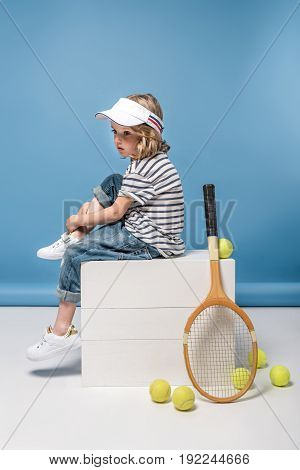 adorable little girl with tennis raquet and balls sitting on white boxes