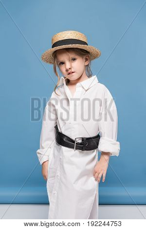 Adorable Little Girl Posing In White Shirt And Straw Boater, Studio Shot On Blue